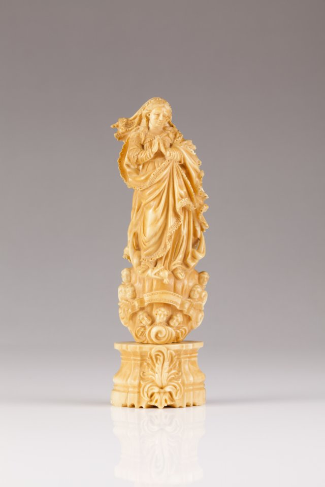 An 18th century Indo-Portuguese ivory sculpture of Our Lady of the Conception Richly carved, on faceted base decorated with feather